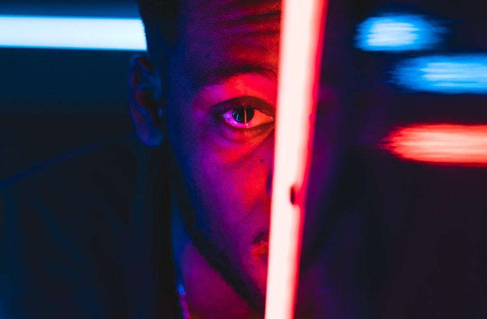 Un hombre mira de frente a traves de un panel de luces de neón