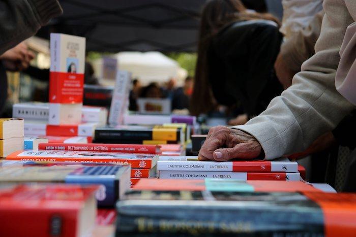 Mujer consulta libros en una parada de Sant Jordi