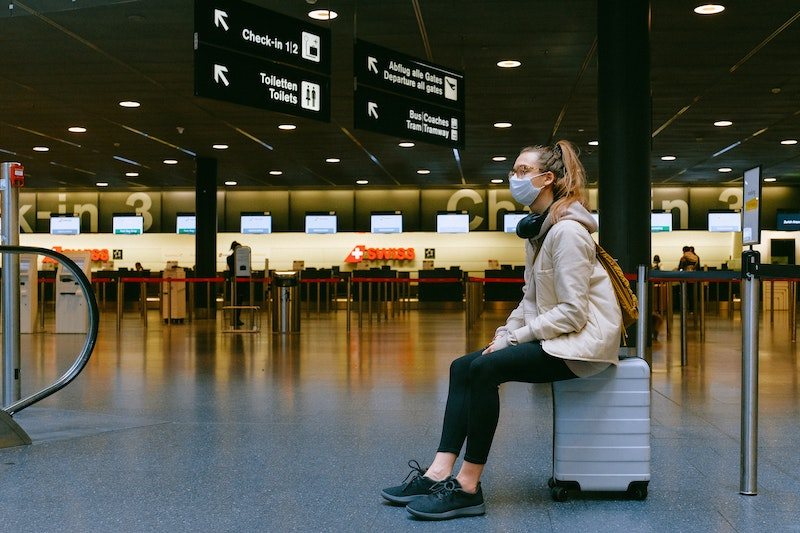 Mujer esperando en el aeropuerto con mascarilla